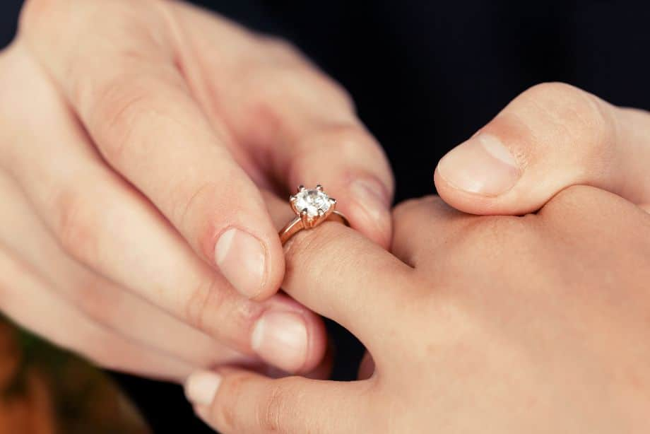 A 14k Rose Gold Engagement Ring Being Placed on a Woman's Ring Finger